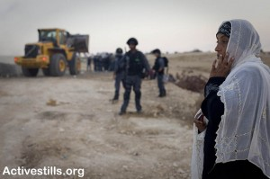 A Bedouin woman looks on as Israeli soldiers demolish  her village of Al Arakib again 13/9/2010